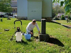 Volunteer cleans headstones in the Tolson's Chapel cemetery.