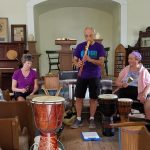 Three members of the Tri-State Drum Circle are performing at the front of the chapel.