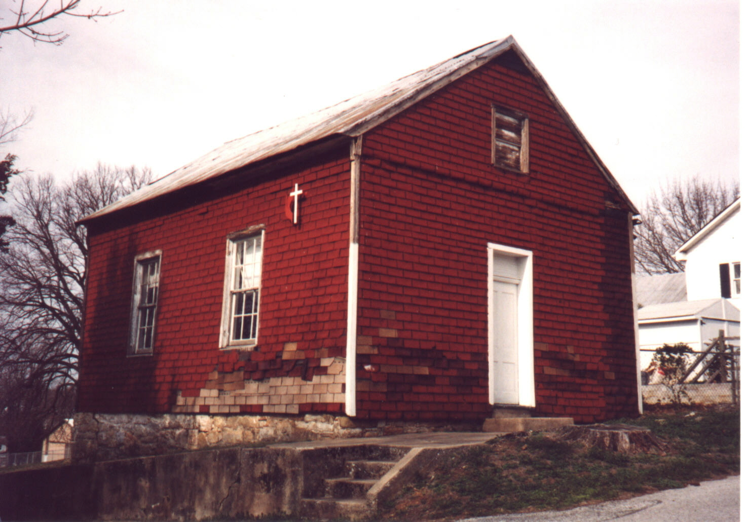 Viewer is facing the chapel, which is painted red.